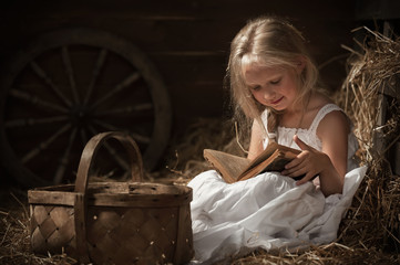 Girl reading a book in the hay