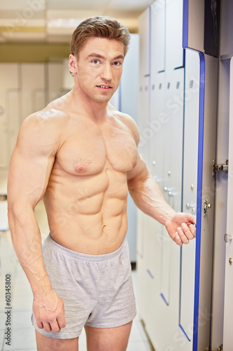Bodybuilder opens locker in locker room after finishing training