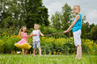 Children prepare to play tug-of-war, focus on boy in blue