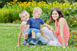 Young smiling woman sits on grass with two little sons on flower