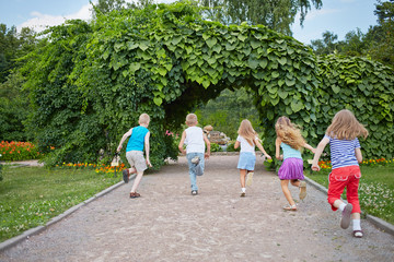 Children run on park walkway into arch made of green plants