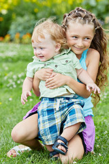 Little smiling girl sits squatted on grassy lawn, holding boy