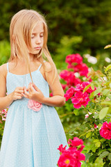 Little girl dressed in polka-dot gown look at rosebush in summer