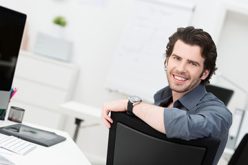 zufriedener mann im büro stützt sich auf stuhl