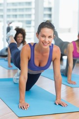 Women doing stretching exercises in fitness studio
