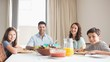 Portrait of happy family of four sitting at dining table