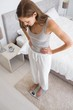 Fit young woman standing on scale in bedroom
