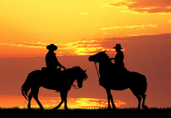 Men on horses ay sunset
