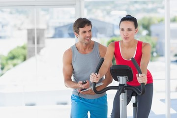 Woman with male instructor working out at spinning class