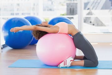 Side view of a fit woman exercising on fitness ball at gym