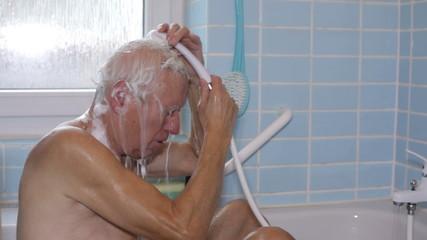 Senior man washing his hair using shower in bath.