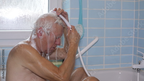 Senior man washing his hair using shower in bath.