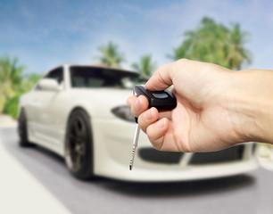 Hand press unlock button against new car