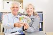 Zwei Senioren halten Euroscheine hoch