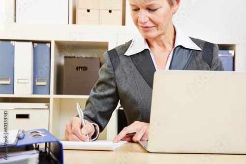 Geschäftsfrau im Büro macht Notizen
