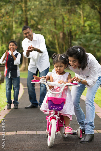 indian family guiding little daughter to cycle