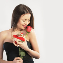 Young woman holding a gift and a flower