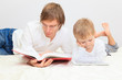 Father reading while son looking at touch pad