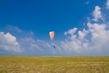 Flying paramotor under blue sky