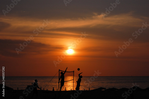 Beach volleyball players' silhouettes at sunset
