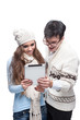 young smiling winter couple using tablet