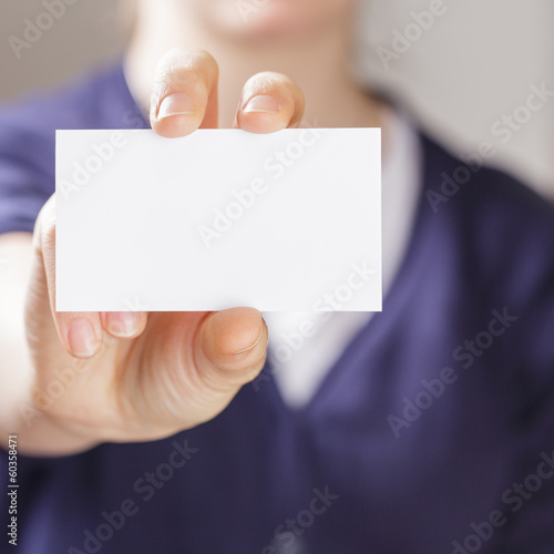 female teen holding empty business card in front of camera
