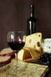 Glass of red wine, and several varieties of cheese