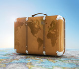 old suitcase on blurred world map and sky in background