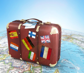 old suitcase with air ticket and striples flags on blurred world