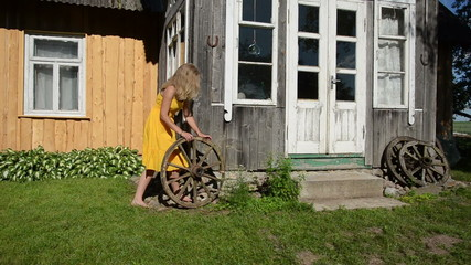Lady in yellow dress rolls old carriage wheel near rural house