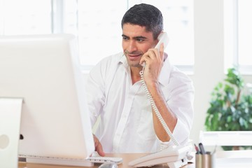 Businessman using computer and telephone