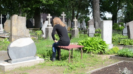 depressed woman sit on bench near husband grave in cemetery