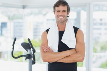 Smiling man standing with arms crossed at spinning class in brig