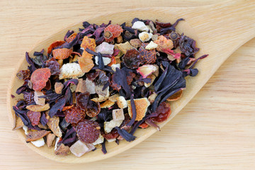 A spoon of dried Fruit tea on a wooden background