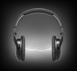 Headphones and lightning on black background