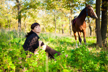 girl and horse in the woods on a background of green grass