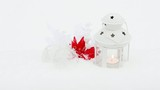 A candle lantern and xmas decoration outdoors in the snowfall