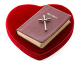 Bible and cross over red velvet heart