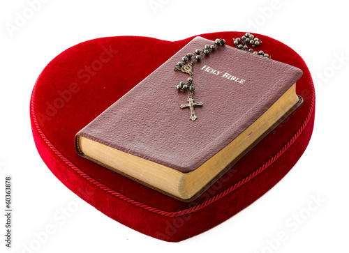 Bible and Rosary over a red velvet heart
