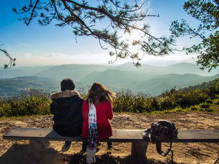 Young couple with backpacks relaxing on top of a mountain