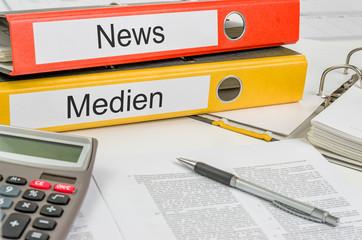 Aktenordner mit der Beschriftung News und Medien