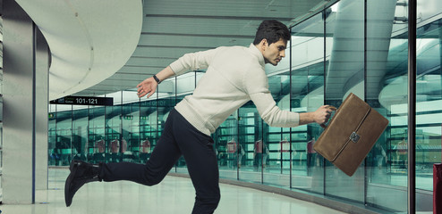 Running businessman with brown suitcase