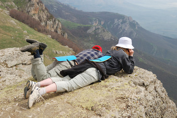 Woman and boy lying on top of mountain.