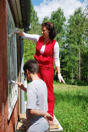 Family repairing house on the outside together
