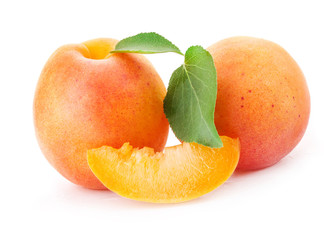 Apricots and slice with green leaves, isolated on white