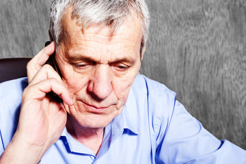 Elderly worried businessman with mobile phone