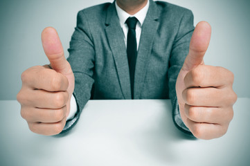 man in suit giving a thumbs up signal