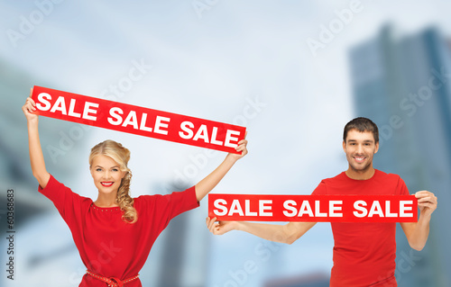 woman and man with red sale signs