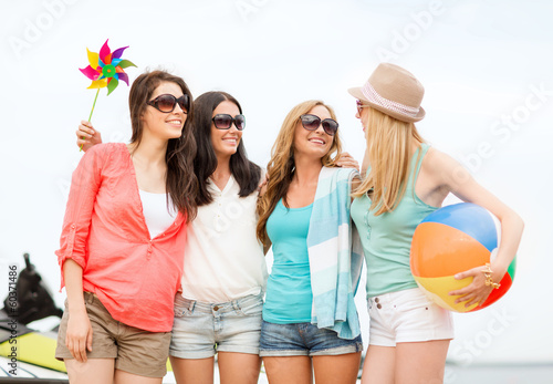 smiling girls in shades having fun on the beach