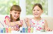 Little girls are painting with gouache